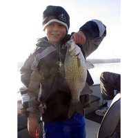 The super young kid holds his nice white bass
